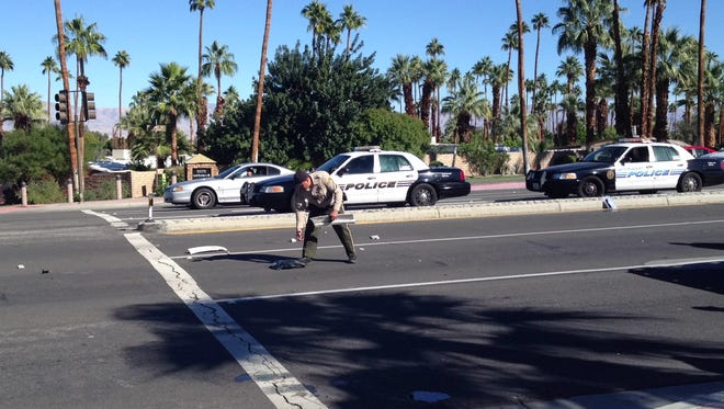 A Riverside County sheriff's deputy removes debris from Highway 111, where a motorcycle collided with a minivan Tuesday.