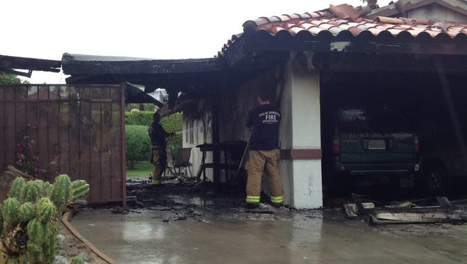 Palm Springs firefighters mop up after a fire on San Mateo Drive Friday morning.