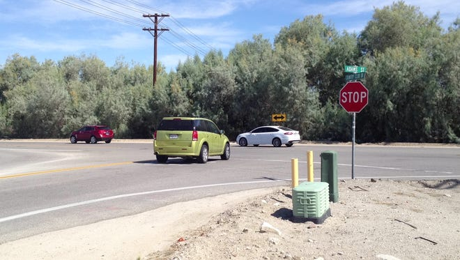 A car waits on Adams Street to turn left onto Country Club Drive in Bermuda Dunes Thursday. Riverside County traffic officials say a signal is necessary and may be installed at the intersection next year.