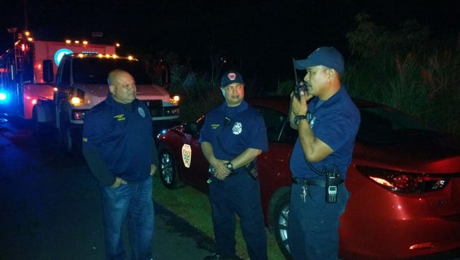 Guam Fire Department firefighters coordinate a search for five lost hikers in the Tarzan Falls area Saturday.
