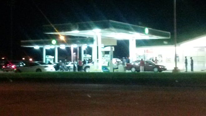 A large group of people gathers at a gas station, yelling at each other.