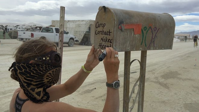 Her face shielded against the dust, a woman decorates a mailbox at Burning Man.