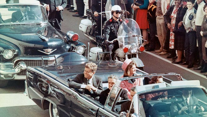 President John F. Kennedy rides in a motorcade in Dallas shortly before his Nov. 22, 1963, assassination.