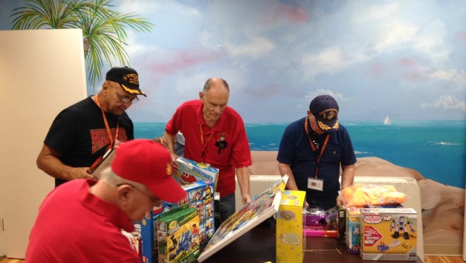 from left, John Anderson, Louis Bonilla, Bob Bloch and Frank Aloe, Members of the Barefoot Bay Marine Corps League, Detachment 918, help sort toys