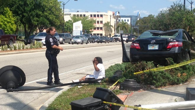 A Fort Myers police officer questions the driver of a car that ran over a crosswalk signal and landscaping at Winkler Avenue and Fowler Street on Monday.