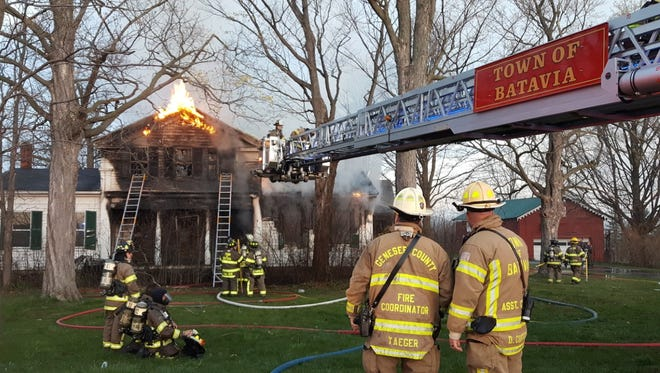 Firefighters battle a house fire in the town of Batavia on April 30, 2016.