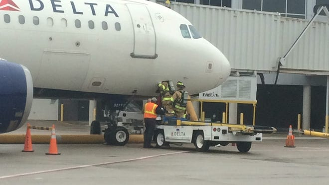 "Firefighters inspect Delta flight 2841 after it made an emergency landing at Green Bay-Austin Straubel International Airport on Tuesday, May 10, 2016, due to a ""smoky odor"" on board."