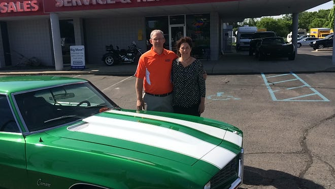 John and Jenny Conely with the one car on their lot not for sale - a classic 1969 Camaro he's own since he was a teenager.