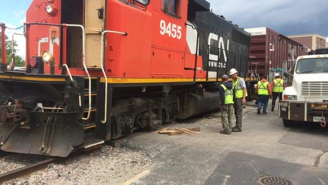 CN employees work on a derailed train engine near Main Avenue in De Pere.