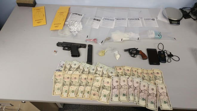 IMPD officers seized 11 grams of cocaine, two guns and cash when serving a search warrant Friday night.