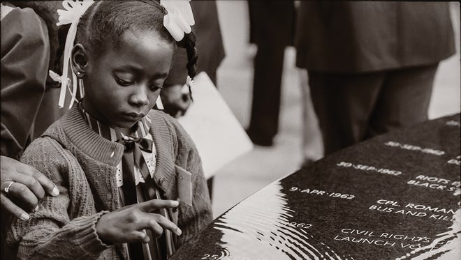 A child touches the water flowing over the Civil Rights Memorial in Montgomery, Alabama. The memorial honors 40 martyrs killed during the civil rights movement.