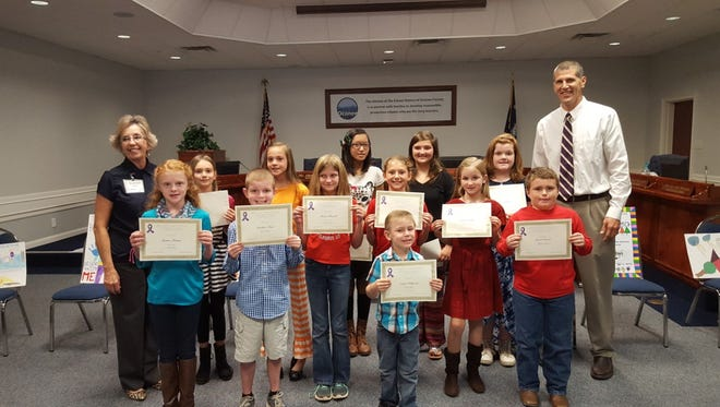 Shown are, in the front row, from left, Jenna Morris, Landon Moss, Evan Williams and Jamon Roach; middle row, from left,  Suzanne Merrill (director, A Call to Action Oconee), Adrianna Lione, Jacie Brucke, Alaina Howell, Braelyn Smith and Isabel Schell; and center back, from left, Ava McDonald, Emma McDonald, Grace Mullen, and School District of Oconee County Superintendent Dr. Michael Thorsland.