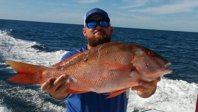 Andrew Border holds up a 27-inch, 13-pound mutton snapper that he caught aboard the KUDU with Capt. Mike Hatcher in the Gulf of Mexico. Borer used squid as bait to catch the fish.