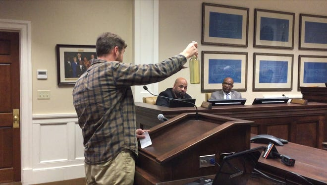 Parkhaven resident Joshua Tillman shows Hattiesburg City Council a bottle of discolored water that came from his tap.