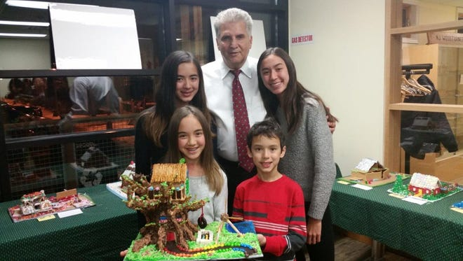 Essex County Executive Joseph N. DiVincenzo, Jr., center, congratulates Ella, Ashlyn, Avery and Hayden McAdams from Montclair for winning second place in the Group/Family Category in the Essex County Environmental Center's 12th Annual Sustainable Homes and Habitats Gingerbread Contest on Tuesday, Dec. 20.