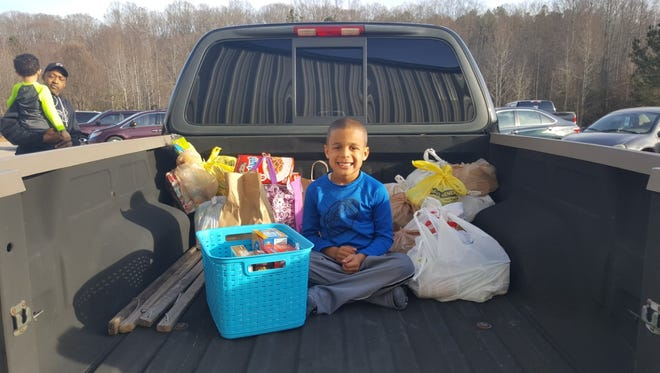 """Zien Jefferson takes a pose with """"birthday donations"""" given to Anderson Interfaith Ministries (AIM) on Feb. 11. Zien chose to receive food for gifts instead of gifts for himself at his birthday party on Feb. 4."""