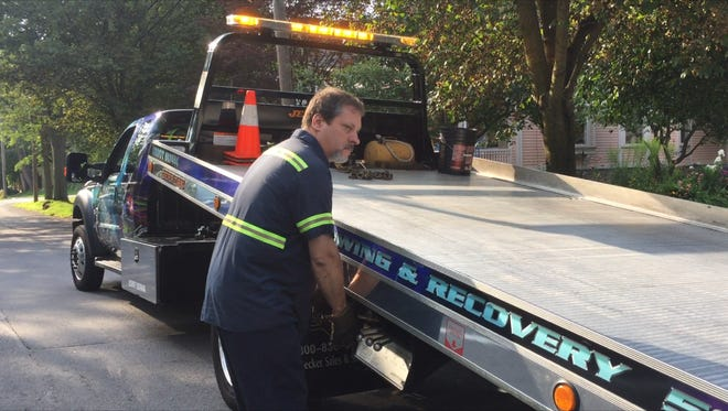 Tow truck driver John McDonald prepares to load a vehicle onto his truck. Tow truck operators are lobbying Albany to allow them to install blue lights on their trucks.