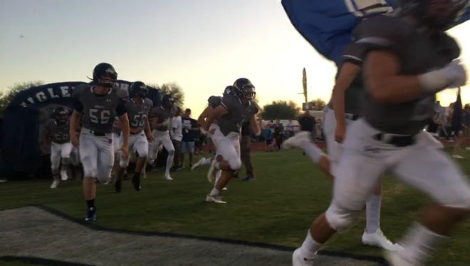 Higley football players charge the field before their game against Mingus.