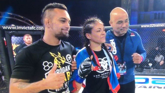In this file photo, Brogan Walker Sanchez, flanked by husband, Mike Sanchez, at left, and instructor and coach Stephen Roberto, right, celebrates her win at Invicta FC 27 in Kansas City, Missouri.