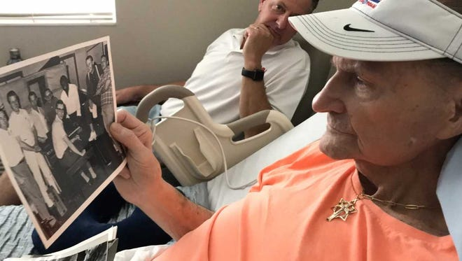 Papa Don Schroeder  looks over old band photos while recuperating at a local rehabilitation facility. Watching on is his son, Scott Schroeder.