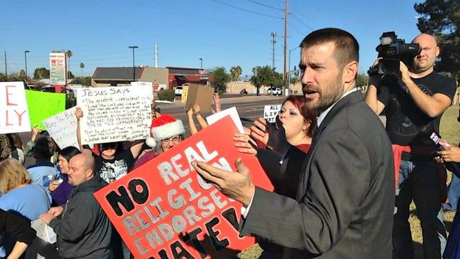 Pastor Steven Anderson addresses demonstrators protesting his sermon outside Faithful Word Baptist Church on Sunday, Dec. 7.