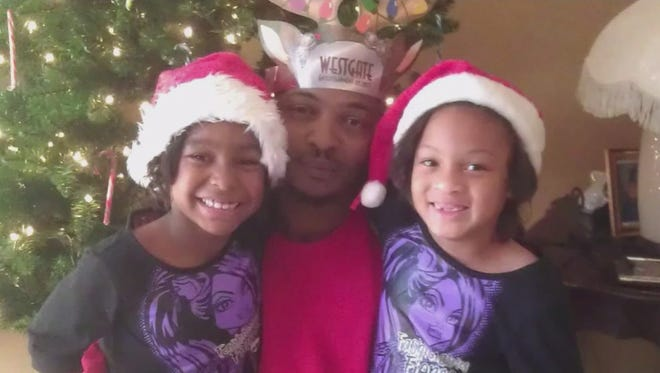 Phoenix shooting victim Rumain Brisbon is shown with his daughters in this undated photo.
