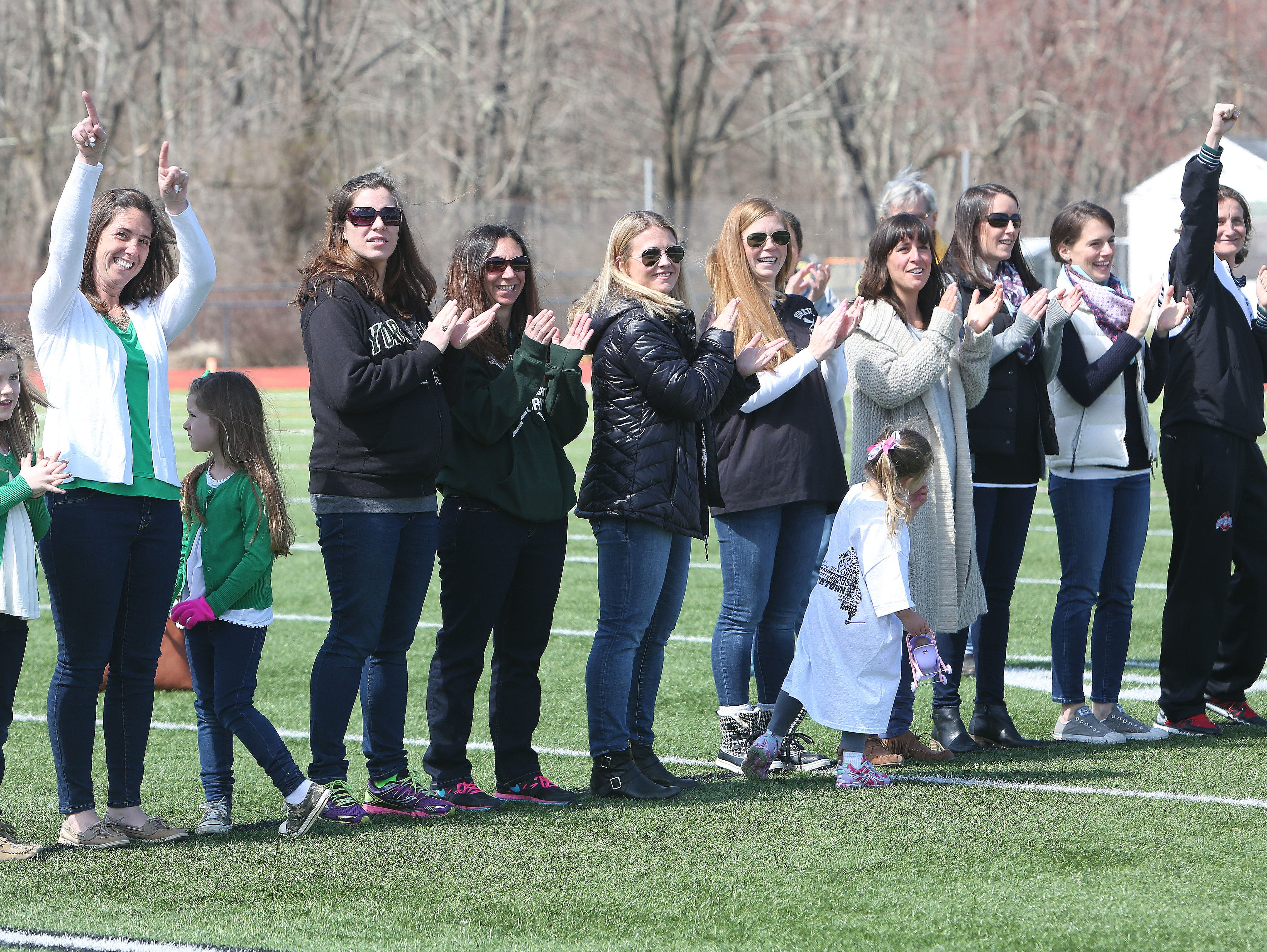 Former Yorktown girl's lacrosse state champions wave to the crowd as they are introduced during a halftime ceremony honoring the past state championship teams at Yorktown High School during game against Arlington March 26, 2016.