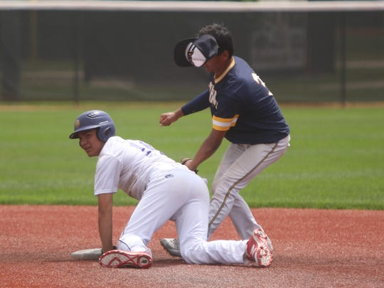 New Berlin Eisenhower freshman Gabe Seifert is tagged out at second base by Whitnall infielder Stephan Flores.