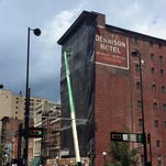 A black cover on the front facade of the former Dennison Hotel in downtown Cincinnati on Friday. Although the cover was added without a permit, city officials are allowing it to stay pending a review of a permit application from Columbia Development Group, the property's owner.