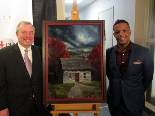 """Memphis in May President Jim Holt, left, with artist Jared Small and his oil-on-board work """"Canada,"""" at the painting unveiling."""
