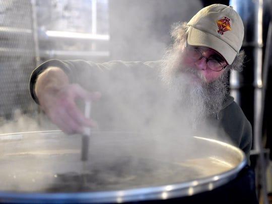 Brewer Jeff Adams works on a batch of beer at Crafty Bastard Brewery.