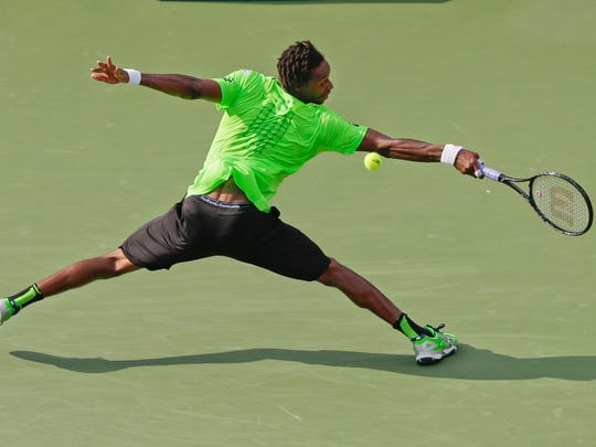 Gael Monfils of France returns a shot against Grigor Dimitrov of Bulgaria during the fourth round of the 2014 U.S. Open tennis tournament, Tuesday, Sept. 2, 2014, in New York.