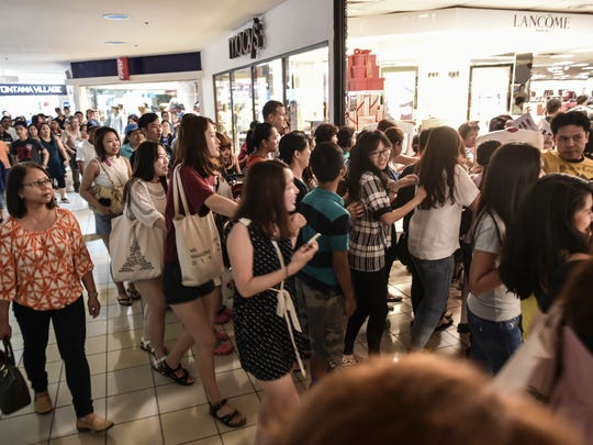 Bargain shoppers flood an entrance to Macy's department store in the Micronesia Mall on Nov. 26, 2015, taking advantage of a one-day head start on Black Friday sales.
