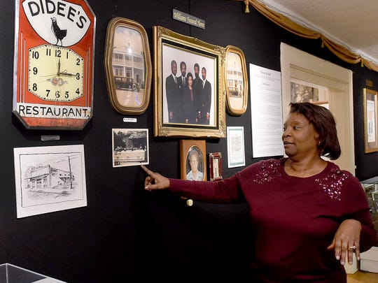 Delores Guillory, director of the Opelousas Museum and Interpretive Center, looks over historic photos of Williams Funeral Home, part of a Black History Month display.
