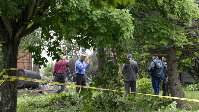 Investigators rope off the site of small airplane crash in the backyard of a home that killed the pilot on Tuesday, June 17, 2014, in East Patchogue, N.Y.  A mother and infant inside the house in the community of East Patchogue were not injured, said Brookhaven Town spokesman Kevin Molloy.