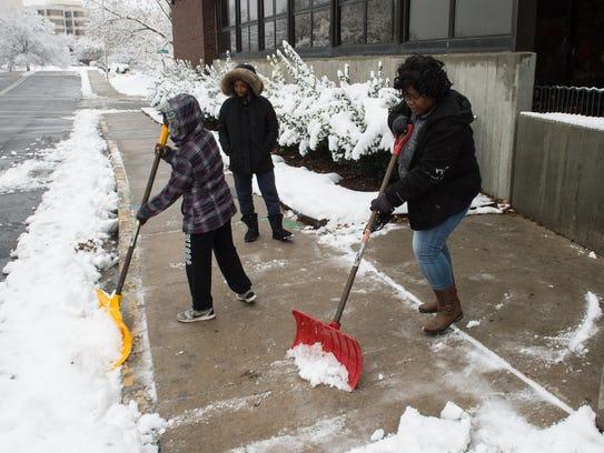 Suzette Davis shovels the sidewalk in front of the