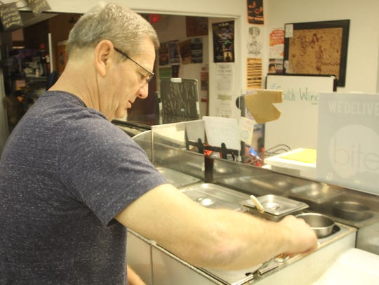 Gary Yost scoops some of his 100-year-old recipe chili,