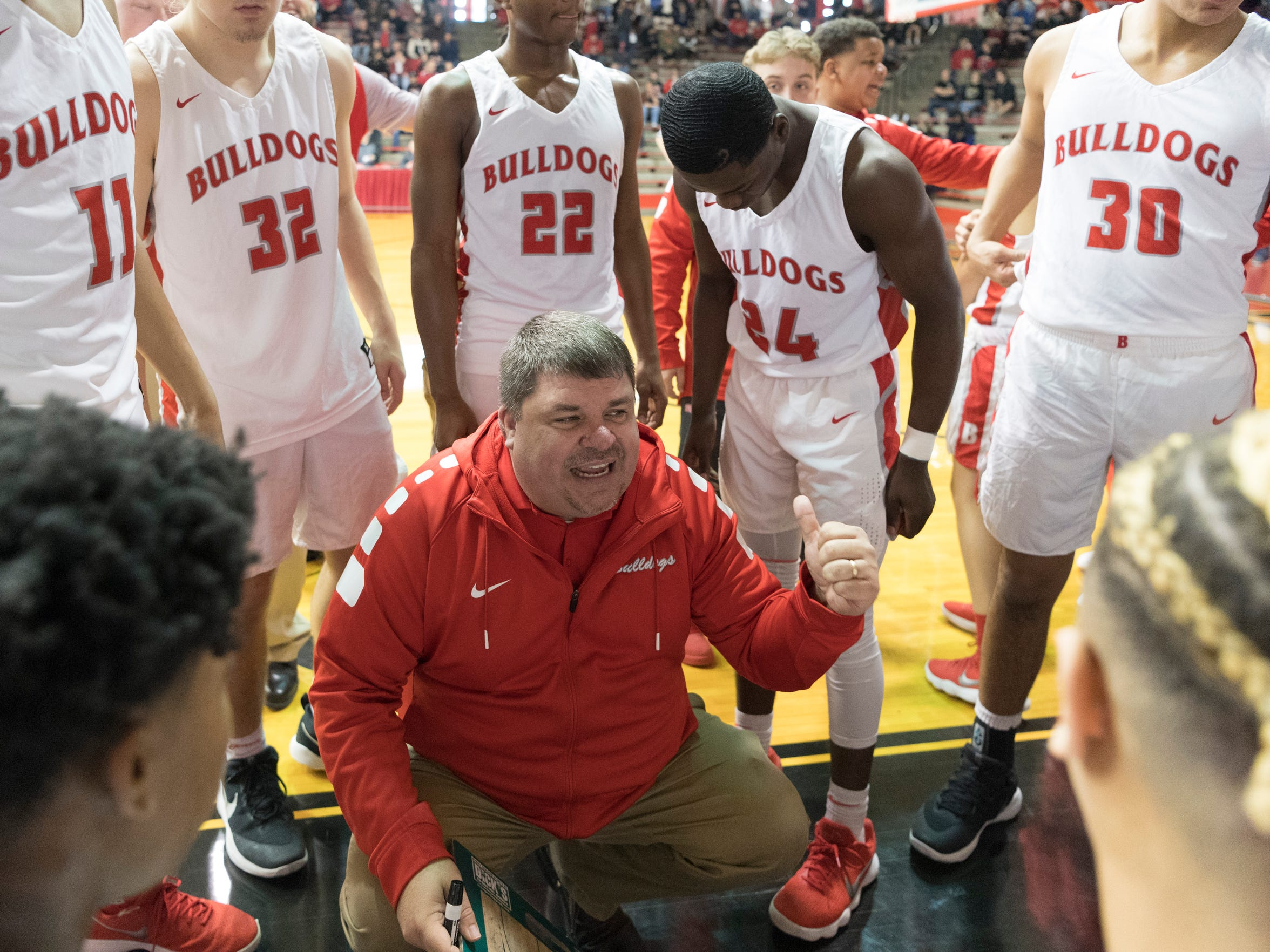 Bosse Head Coach Shane Burkhart talks to his team during a timeout in the first game of the IHSAA Class 3A Regional Tournament at Memorial Gym in Huntingburg, Ind., Saturday, March 10, 2018. The Bulldogs defeated the Pirates, 75-58, to advance to the evening's Regional Championship game.