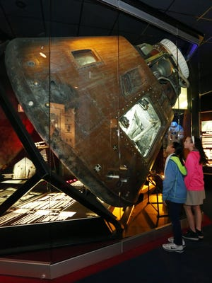 Hutchinson Magnet School at Allen students Jordan Bell, left, and Chauntea Grissom peek into the Apollo 13 capsule in this April 2015 file photo. The Cosmosphere will now mark the anniversary of the Apollo 13 mission with an online auction.