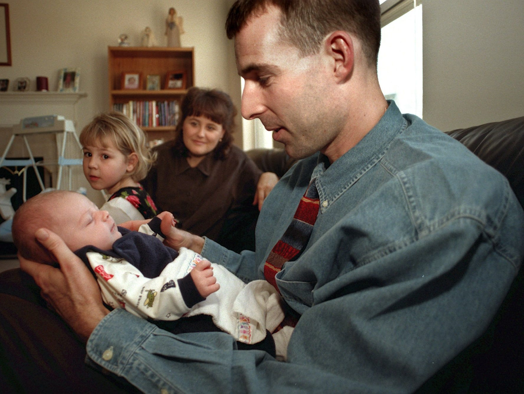 In this 1999 file photo, Greg Mitchell sits with his then-three-week-old son Bryson and his daughter Aleah, 5, and wife, Dina, look on.
