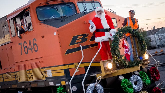 Santa Claus arrives via train at the Las Cruces Railroad Museum on Friday evening.