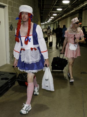 This Sept. 24, 2008 file photo shows Oakland Athletics rookie pitcher Brad Ziegler, left, heading to board the team bus after their 14-4 loss to the Texas Rangers in baseball game in Arlington, Texas. That hazing ritual of dressing up rookies as Wonder Woman, Hooters Girls and Dallas Cowboys cheerleaders is now banned. Major League Baseball created an Anti-Hazing and Anti-Bullying Policy that covers the practice. As part of the sport's new labor deal, set to be ratified by both sides Tuesday, Dec. 12, 2016 the players' union agreed not to contest it.