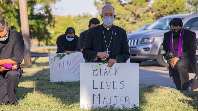 Bishop Mark Seitz, center, kneels with other demonstrators June 1 at Memorial Park holding a Black Lives Matter sign in El Paso, Texas. Pope Francis called Seitz unexpectedly after he was photographed at the protest.