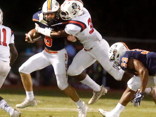 Blackman's quarterback Connor Mitchell (6) runs the ball as Oakland's Aaro(n Moore 36) brings him down with a tackle, on Friday, Sept. 22, 2017, at Blackman.