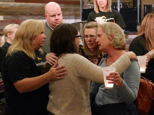 At the end of the candlelight vigil for Meredith Furr friends gather around her motherMistio. Furr was a fourth-grader at Guy K. Stump Elementary School. The service was held at the Destiny Family Center, Stuarts Draft Sunday March, 13, 2016. Furr died after a difficult fight with cancer.