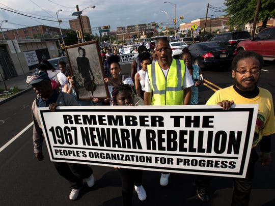 "Marchers on Irvine Turner Boulevard hold signs in remembrance of the ""Newark Rebellion."""