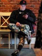 Tim Hunter, of Port Huron, sits down while wearing a pair of leggings Sunday, Jan. 31, during a boutique pop-up shop featuring LuLaRoe clothing by Suzy and Steph at Kate's Downtown.