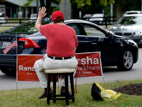 Campaign volunteer Jim Barker waves to motorists as they drive by the Brentwood Library polling location during the primary election on Aug. 2.