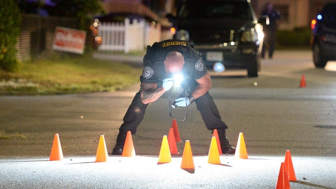 In this Aug. 4, 2020, file photo, a sheriff's deputy with the Plymouth County Bureau of Criminal Investigation takes photos of shell casings, marked by orange cones, in the road on Kenwood Street in Brockton after 17 gunshots rang out.