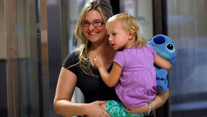 Athena Manuma walks through Phoenix Sky Harbor International Airport with her daughter Ava Enlow, 2, on Tuesday, April 3, 2012, after the girl was taken to Mexico by her father.